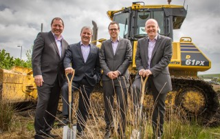 image of four wcctv directors in front of a bulldozer at the site of their new premises
