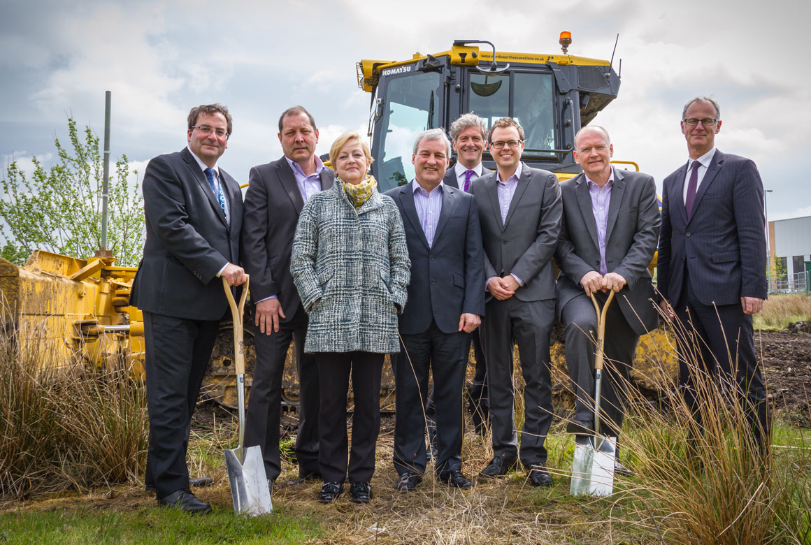 Image of dignitaries in front of a stationary bulldozer at Kingsway Business Park